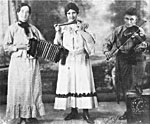 Photograph of Albertine Villeneuve with accordion, Mary Bolduc with harmonica and Gustav Doiron with fiddle