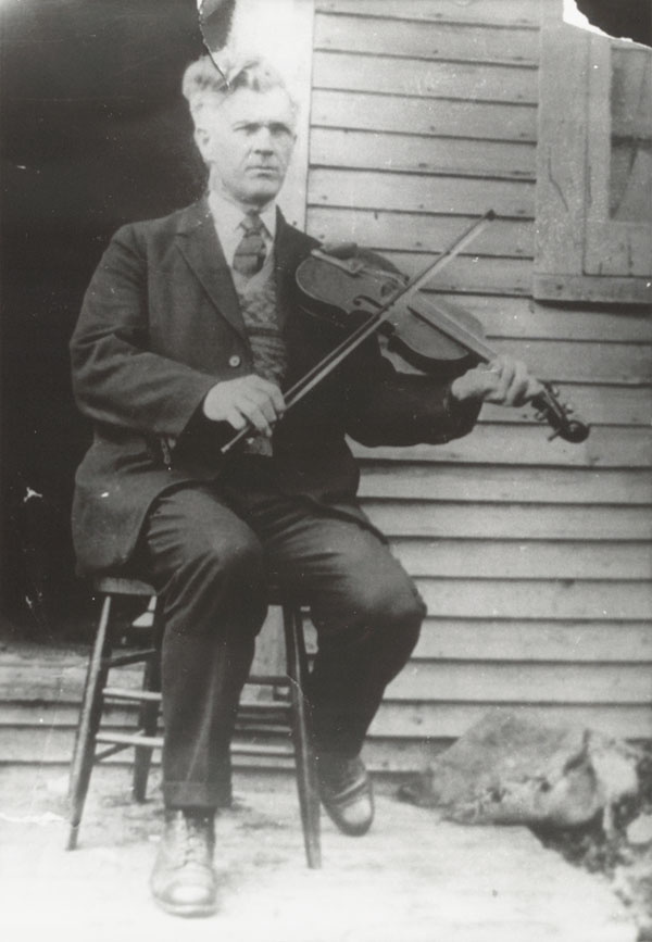 Photograph of an older Joseph Allard, seated, playing the fiddle