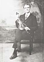 Photograph of J.O. LaMadeleine, seated and holding his fiddle, undated