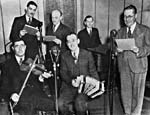 Photograph of Conrad Gauthier with Isidore Soucy, Donat Lafleur, Henri Leduc, Alfred Vallerand and René Delisle broadcasting a radio show from CHLP entitled À LA BRUNANTE, March 1941