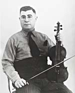 Photograph of Isidore Soucy, seated and holding his fiddle