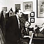 Photograph of Donalda at her piano, with Robert Savoie standing beside her and singing