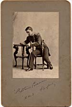 Photograph of young George MacFarlane as Captain Corcoran in HMS PINAFORE, sitting at a table reading