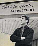 Photograph of Stan Klees in front of a sign reading, WATCH FOR UPCOMING PRODUCTIONS