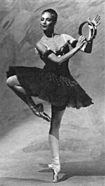 Photograph of Evelyn Hart, in a tutu and pointe shoes, holding a tambourine