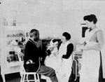 Photo du Dr Wilfred Grenfell examinant un jeune patient de l'hôpital, vers 1905-1915, Harrington Harbour [Québec]
