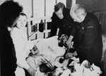 Photograph of Dr. Norman Bethune, assisted by Henning Sorensen, performing a blood-transfusion during the Spanish Civil War