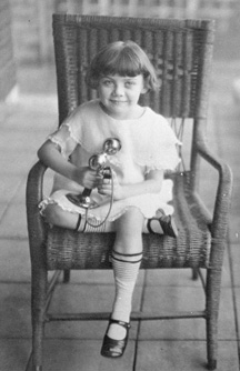 Photograph of a young girl sitting in a chair, holding a telephone, early 20th century, by John Kelso
