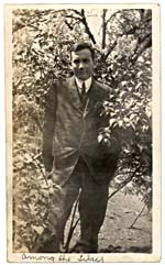 Photograph of Harold Innis standing among lilacs, no date