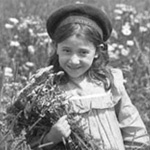 Photograph of a girl standing in a field of daisies, Cap l'Aigle, Quebec