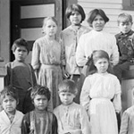 Photograph of a group of Aboriginal students and a dog on the steps of the residential school near Woodstock, New Brunswick