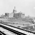 Photograph of the provincial government buildings with train tracks and some buildings in the foreground, Edmonton, Alberta, 1914