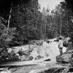 Photograph of a river with rapids surrounded by a forest, probably the Gatineau Hills, Quebec, ca. 1865-1880