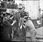 A wounded soldier is carried off the ship upon his return to England.