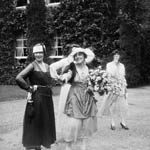 Photograph of several women in dresses and hats, one holding a bouquet of flowers, circa 1914-1918