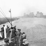 Photograph showing a group of passengers at the bow of a ship as it approaches the Canadian Pacific railway grain elevators, Fort William, Ontario, date unknown