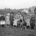Photograph of nine children and a dog in a turnip field at the Peabody Brothers Farm, Woodstock, New Brunswick, 1912