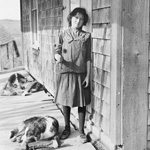 Photograph of a young woman standing on a porch and holding a flower while her dog stretches out at her feet, Woodstock, Ontario, date unknown