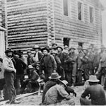 Photograph of a large group of men lined up outside a two-story log building, Dawson, Yukon, 1898