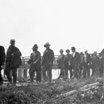 Photograph of a group of men picketing along a boardwalk near a pier and buildings, Steveston, British Columbia, 1900