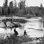 Photograph of two men fishing beside a river, River aux Sables, Ontario, 1876