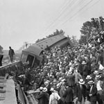 Photograph of three derailed train cars, with inspectors standing on one of the cars while a large crowd looks on, Ottawa, early 1900s