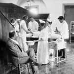 Photograph of doctors and nurses operating on a patient while a man looks on from a chair, Halifax, Nova Scotia, circa 1898-1907