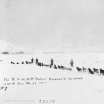 Photograph of five men and their dogsleds crossing a snow-covered lake or flat land, near Dawson City, Yukon, 1909