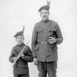 Photograph of two military men, one tall, the other very short and holding a flute, 1915