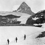 Photograph showing four men crossing an ice field while climbing Mount Assiniboine, Alberta-British Columbia border, date unknown