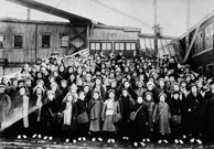 Black and white photograph of a large group of children standing on a wharf