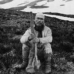 Photograph of an Aboriginal man holding a gun, seated at the summit of Groundhog Mountain, British Columbia, 1899