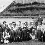 Photograph of a group at a Ukrainian wedding posed in front of a house with a thatched roof, 1911