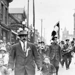 Photograph showing two men and two boys walking in the street in front of a marching band, Toronto, circa 1914-1918