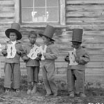 Photograph of students at the Fort Simpson Indian Residential School standing in front of the wooden school, each holding up a paper letter spelling, together, the word GOODBYE, Fort Simpson, Northwest Territories, circa 1922