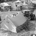 Photograph of a campground, showing tents and cars, date unknown