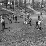 Photograph of a group of young people playing with hockey and lacrosse sticks in a field or park, date unknown
