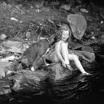 Photograph of a smiling girl sitting on a rock beside a lake, while her dog gives her a kiss, Bala, Ontario, 1933