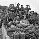 Photograph of a group of nursing sisters and soldiers in military uniforms riding in the back of a truck, Arromanches, France, 1944