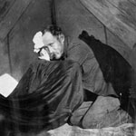 Photograph of Dr. W.H. Ellis, kneeling in a tent, Nipissing or Timiskaming district, Ontario, 1897