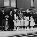 Photograph of the Dionne Quintuplets as young girls, on a train platform with their parents, nurses, Dr. Dafoe and a male guardian, date unknown