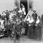 Photograph of female and male Aboriginal students, nuns and two men outside an Indian residential school, circa 1890