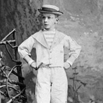Photograph of a boy in short pants, a sailor top, hat and striped socks posing in a studio, Québec, date unknown