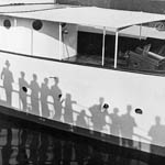 Black and white photograph of a boat with shadows of people leaning against the railing of another ship projected onto the side of its hull, and their reflection in the water below