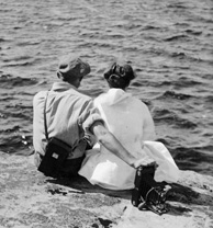 Photograph of a man and a woman, each with a camera, sitting on a rock on the shore of a lake with their backs to the photographer, Sparrow Lake, Ontario, 1916