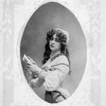 Postcard, reading BONNE FÊTE, on which appears a photograph of a woman holding a book, circa 1912