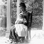 Photograph of a woman, Mrs, Rowland, sitting on a rocking chair on a porch with a baby in her lap, Ottawa, 1891