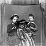Photograph of two girls and a boy posed front of a blanket fastened to the side of a wooden building, Ottawa, 1892