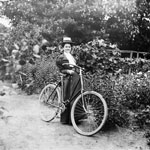 Photograph of a young woman, Mabel Williams, standing beside her bicycle on a garden path, Ottawa, 1898