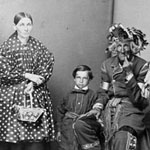 Photograph showing three men, a woman and a boy in traditional Aboriginal clothing, Lorette, Quebec, 1880